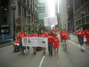 group of people in red shirts with organizational banner walking and rolling up street in a parade