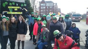 Image of a group of people dressed in warm coats, wearing green bowler hats, standing and seated in wheelchairs, looking at the camera