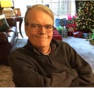 image of man seated, with arms crossed, smiling for camera. Man is wearing sweater and glasses. In background are holiday tree, gifts, and couch