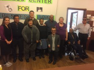 A photo of Progress Center Board Members and Staff Members. People in the image are lined up in two rows against conference room wall. Linda Marek is standing just to the left of the door frame.