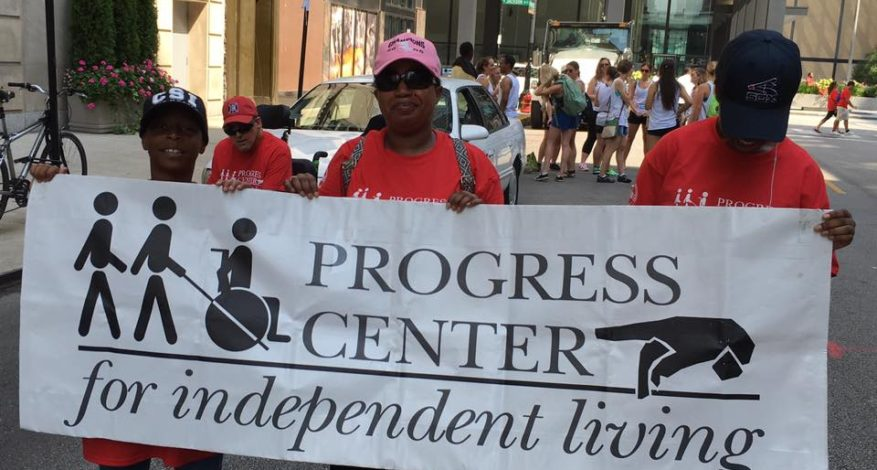 image of three people who are African American. The three people are holding a Progress Center banner at the Disability Pride Parade.
