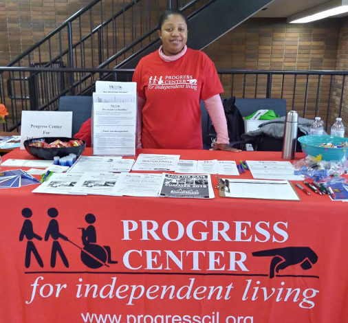 image of woman standing behind Progress Center resource table. Table has red covering and information packets are laid out across the table