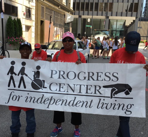 Three Progress Center supporters holding the Progress Center Banner at the Disability Pride Parade