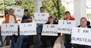 "Image of group of people, all holding signs that read ""I am Olmstead."""