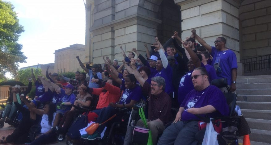 image of group of people standing and in chairs on steps of capitol in Springfield with fists raised