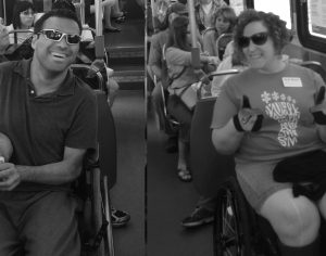 image of passengers on a bus. Passengers in foreground seats appear to be disabled and are smiling for the camera.