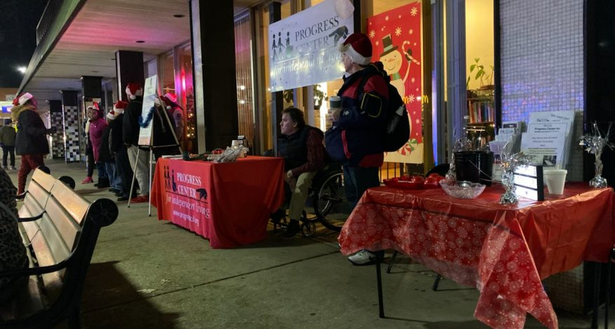 Image of tables and people outside the Progress Center Office in early December 2019, the Forest Park Festival of Lights Event