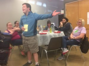 image of adult standing before a table, speaking and motioning. Table behind person is filled with other people, watching and listening. Photo from 2019 Membership Luncheon