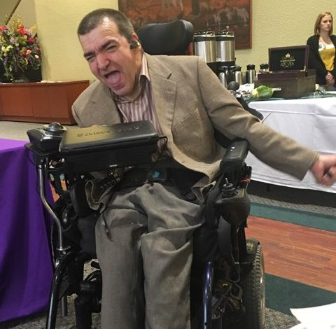 image of caucassion male wearing grey slacks and a tan sport coat, sitting in a power wheelchair